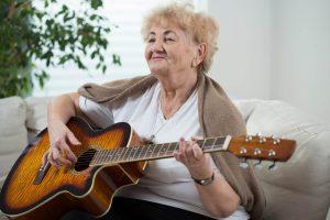 Résidente jouant de la guitare au sein de la Résidence retraite Lyna